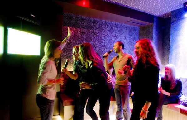 This is a picture of 8 people in a karaoke room in Paris.