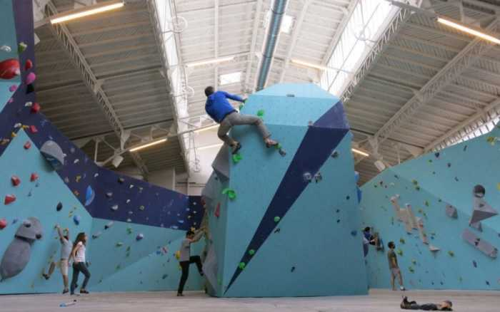 This is a picture of the interior of Arkoze, where people are climbing, which is nice activity to do in Paris.