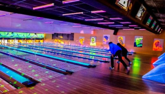 This is a picture of 2 people playing at bowling on Paris.