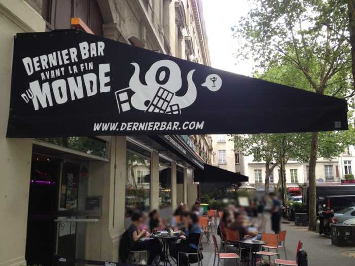 This is a picture of the exterior of le dernier bar avant la fin du monde, which is a nice place to play and have a drink in Paris. And people are chatting on the terrace.