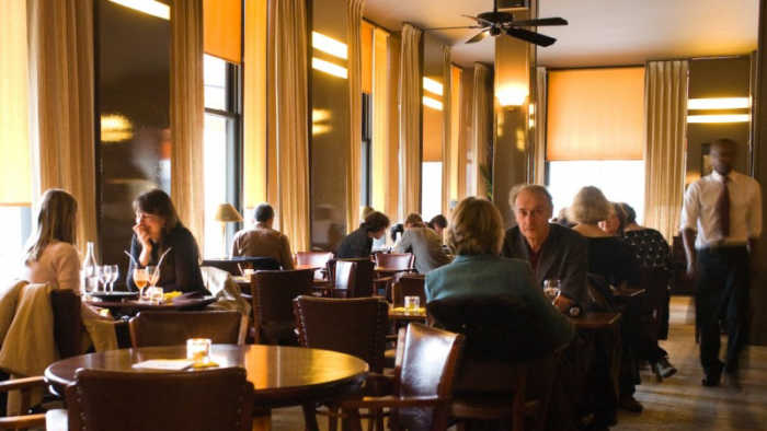 This is a picture of the interior of le fumoir at Paris, with people eating and chatting.