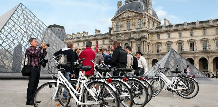 This is a picture of a group of people behind bikes at the Louvres, Paris.