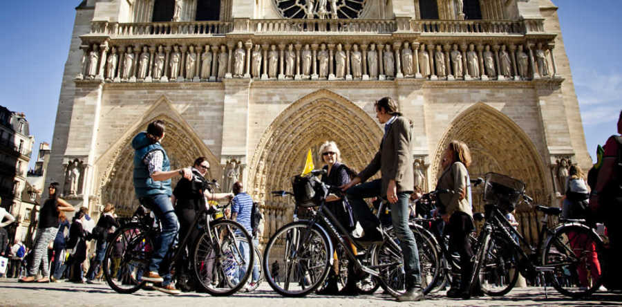 This is a picture of 6 people biking in front of Notre Dame in Paris