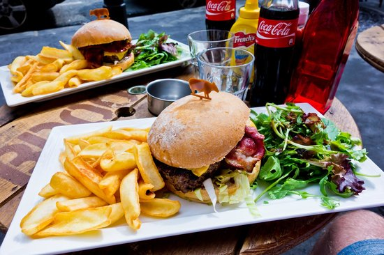 This is a picture of hamburgers fries and coca-cola in a restaurant in paris.